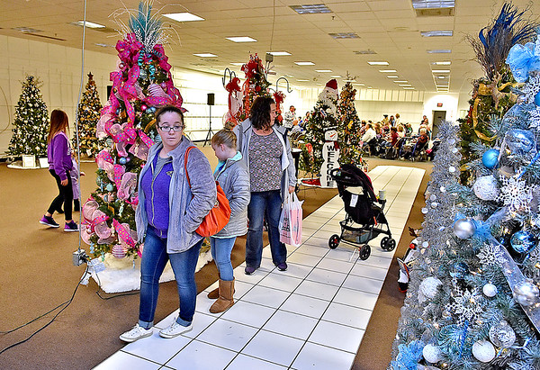 (Brad Davis/The Register-Herald) Visitors browse the selection of specially themed Christmas trees available as the auction for them goes on in the background during the United Way of Southern West Virginia's annual Wonderland of Tree charity event Friday night inside the Crossroads' Mall.