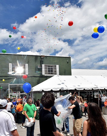 (Brad Davis/The Register-Herald) Hundreds of balloons are released into the air, many with special messages written on them in memory of friends and loved ones lost in last year's flooding, during a family fair in the Old White Motors parking lot Saturday afternoon in White Sulphur Springs.