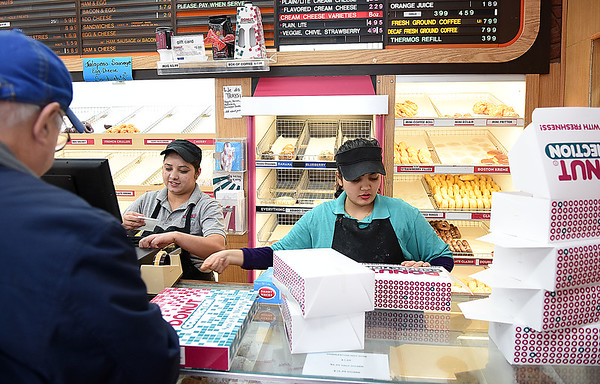 Sargat Dahal Thapa, left, and Preshma Dhakal, waiting on a customer at the Donut Connection<br /> (Rick Barbero/The Register-Herald