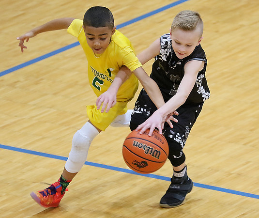 (Brad Davis/The Register-Herald) Huntington Gold's Tristan Hornbuckle, left, and Tug Valley's Brayden Ferral rce for a loose ball at midcourt during 4th grade Biddy Buddy action Saturday at the YMCA.