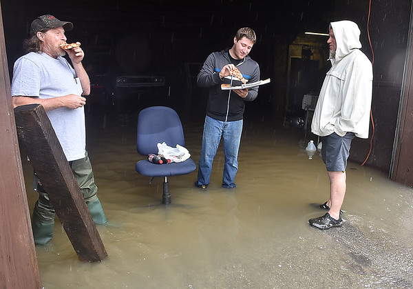 (Brad Davis/The Register-Herald) Scarbro Loop Road residents Ralph Smith, right, Nicholas Clark, right, and a fellow neighbor make the best of a rough situation and chow down on some pizza as flood waters flow through a storage building Monday afternoon.
