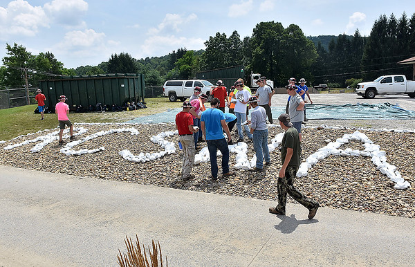 (Brad Davis/The Register-Herald) Scouts from multiple troops out of Illinois finish up a landscaping project at the Raleigh County Solid Waste Authority Thursday afternoon in Beckley.