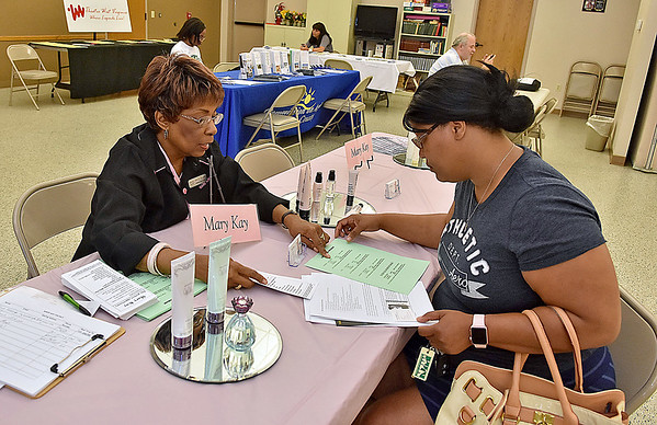 (Brad Davis/The Register-Herald) Lameesha McNeil (right), gets information from Mary Kay Independent Consultant Ann Coleman, one of several representatives from local businesses that were on hand during Heart of God Ministries' Job Connection Fair Saturday afternoon at the Raleigh County Commission on Aging. McNeil just moved to Beckley from Charleston and visited the fair to see what kind of opportunities are out there as she continues her job hunt.