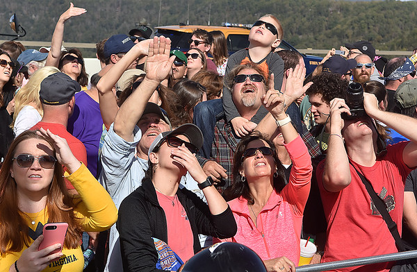 (Brad Davis/The Register-Herald) Spectators battle the sun as they watch and react in a variety of ways to B.A.S.E. jumpers being flung in the air by a catapult, doing tricks off a diving board or jumping from even higher off a hydrolic lift during Bridge Day Saturday afternoon.