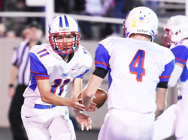 MIidland Trail's Samuel Dickerson (11) hands off to Nathan Hanshew (4) during the opening kickoff for a long kickoff return against Nicholas County Friday in Summersville. (Chris Jackson/The Register-Herald)