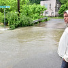 (Brad Davis/The Register-Herald) Scarbro Loop Road resident Ralph Smith looks on as flooding persists after heavy rains in the area Monday afternoon.