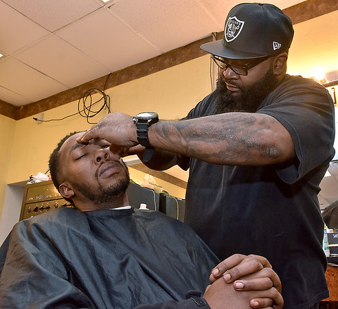 "(Brad Davis/The Register-Herald) Beckley resident Frank Poindexter gets a straight-razored beard trim and a haircut from Beckley Barber Shop owner Sean ""Slugg"" Stevens at the shop's 130 South Heber Street location Wednesday afternoon."