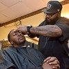 """(Brad Davis/The Register-Herald) Beckley resident Frank Poindexter gets a straight-razored beard trim and a haircut from Beckley Barber Shop owner Sean """"Slugg"""" Stevens at the shop's 130 South Heber Street location Wednesday afternoon."""