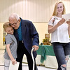 (Brad Davis/The Register-Herald) Harlan Mann, turning 100 years old next week, is greeted by great grandchildren Hayden Phillips (left), 9, and Lyric Noel, 13, during the opening moments of an early birthday party for him thrown by family at Beckley Regular Baptist Church Saturday evening.