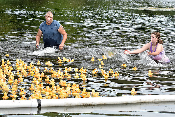 (Brad Davis/The Register-Herald) Race officials Mike Cox and daughter Courtney keep the duckies on course during this year's installment of the CFM House Museum's Great Rubber Ducky Race Sunday afternoon underneath the Veterans Bridge.