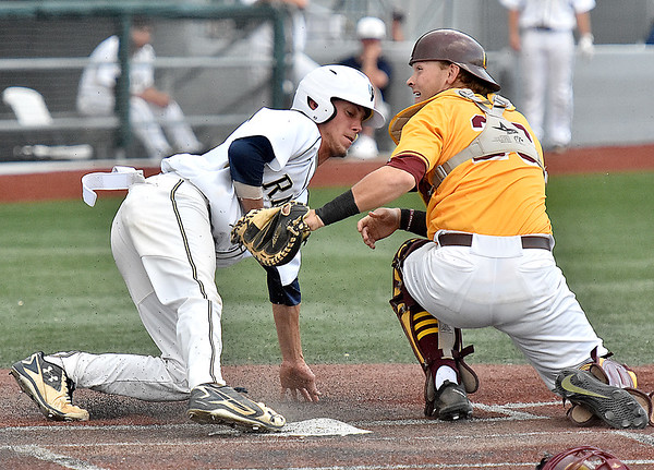 (Brad Davis/The Register-Herald) Shepherd's Trenton Burgreen tries to avoid the tag from Charleston catcher Steven Davis as he tries to score on a wild pitch during the Mountain East Conference Championship game Sunday evening at Linda K. Epling Stadium. Burgreen would be called out on the play.