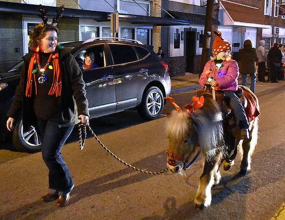 (Brad Davis/The Register-Herald) Mom Kellie Pittman guides as three-year-old daughter Brayleigh rides Scamper the mini horse during the annual Oak Hill Christmas Parade Saturday evening.