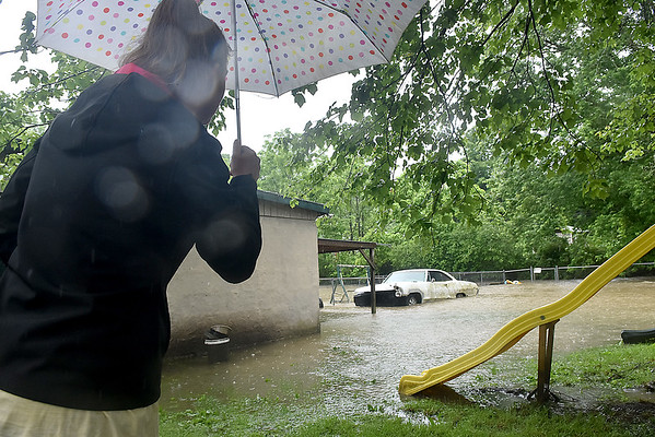 (Brad Davis/The Register-Herald) Scarbro Loop Road resident Jessica Robinson looks on as flooding persists after heavy rains in the area Monday afternoon.