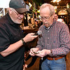 (Brad Davis/The Register-Herald) Groovy 94.1 radio host Ted Morro, left, watches as Beckley resident Bill Eades counts the money he collected after winning a chance inside the United Bank money machine during Celebrity Night at Foster's May 8. Eades managed to grab nine dollars.