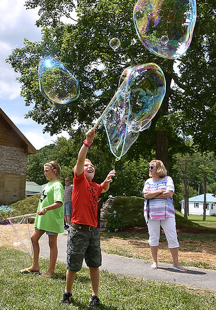 """(Brad Davis/The Register-Herald) Eight-year-old Remington Scott has some fun making huge bubbles where a public """"bubble cart"""" was set up in Old Mill park next to the new memorial during a family fair Saturday in White Sulphur Springs."""