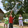 "(Brad Davis/The Register-Herald) Eight-year-old Remington Scott has some fun making huge bubbles where a public ""bubble cart"" was set up in Old Mill park next to the new memorial during a family fair Saturday in White Sulphur Springs."