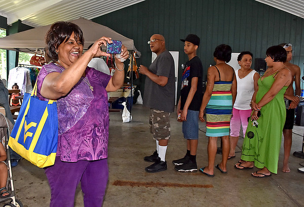 (Brad Davis/The Register-Herald) Juneteenth Committee president Connie McKeever takes photos of the 13th Annual Juneteenth Family Cookout Sunday afternoon at New River Park.