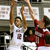 (Brad Davis/The Register-Herald) Woodrow Wilson's Josiah Walton shoots from three-point range as Hurricane's Braxton Dobert defends during the Flying Eagles' win over the Redskins Saturday night at the Beckley-Raleigh County Convention Center.