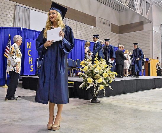 (Brad Davis/The Register-Herald) Graduating Nicholas County High School seniors collect their diplomas and stop, if compelled to by waitng family, for quick snapshots during the school's 103rd Commencement Ceremony Sunday afternoon at the Summersville Arena