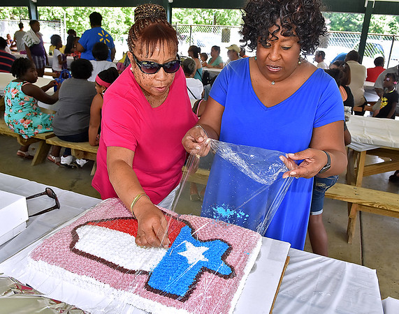 (Brad Davis/The Register-Herald) Juneteenth Committee treasurer Vanessa Burks, left, helps baker Angie Booker as she brings over a special cake with the state of Texas on it during the opening moments of the 13th Annual Juneteenth Family Cookout Sunday afternoon at New River Park. The state of Texas is important in the history of Juneteenth, the oldest known nationwide celebration commemorating the end of slavery in United States. On June 19th, 1865, Union soldiers led by Major General Gordon Granger landed at Galveston, Texas with news that the Civil War had ended and all slaves were now free, a full two and a half years after President Lincoln's Emancipation Proclamation, which became official January 1, 1863 but had little effect on Texans due to minimal numbers of Union troops stationed in the state. It was after General Lee's surrender in April of 1865 when the U.S. was able to get enough soldiers there to enforce the executive order, though several other thoeries on why there was such a delay are still debated among historians today.