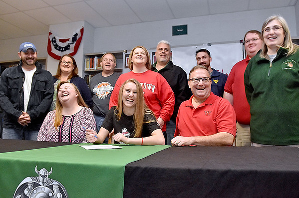 (Brad Davis/The Register-Herald) Wyoming East basketball player Gabby Lupardus, middle, shares some laughs with family, friends and coaches surrounding her as she signs her official letter of intent to play her college ball at D-1 Youngstown State during a ceremony in the school's library Wednesday afternoon in New Richmond.