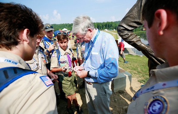 Mike Goodrich, who Goodrich Lake is named after, signs badges following a statue unveiling in front of the lake Thursday during the 2017 National Jamboree at The Summit Bechtel Reserve near Mt. Hope. (Chris Jackson/The Register-Herald)