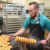 Paul Plumley preparing to glaze donuts at the Donut Connection.<br /> (Rick Barbero/The Register-Herald