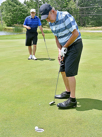 (Brad Davis/The Register-Herald) Participant Charlie Lane sinks his putt as son Phil looks on from behind, part of a foursome that included themselves, Mike Darby and Eric Floresca (both not photographed) during the 20th Annual YMCA of Southern West Virginia Golf Outing Thursday afternoon at Grandview Country Club in Beaver. Over 100 golfers made up around 25 teams that took to the course to raise funds for youth programs offered by the YMCA. Appalachian Power, Chic-fil-A, Pasquale's and Spartan Sporting Goods sponsored the event.