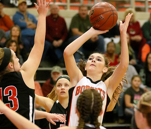 (Brad Davis/The Register-Herald) Summers County's Hannah Taylor pulls up for a short-range shot as Chapmanville's Madison Ward (#13) defends during the Lady Bobcats' win over the Tigers Saturday night in Hinton.