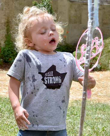 (Brad Davis/The Register-Herald) Three-year-old Lanti Lester takes in a deep breath before blowing a bubble during Saturday afternoon's Family Fair in White Sulphur Springs.