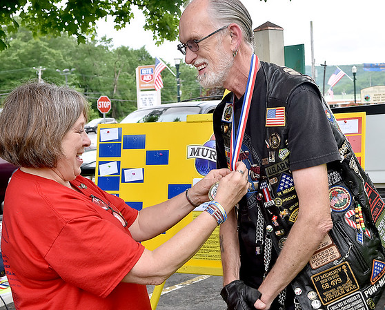 (Brad Davis/The Register-Herald) Army veteran Stretch Wyatt gets his first place medal from organizer and L.Z. Rainelle's Emma Michelinie after defeating Rainelle Station 60 Firefighter Conrad Boggs in a first responder vs veterans murbles tournament Sunday afternoon in Rainelle.
