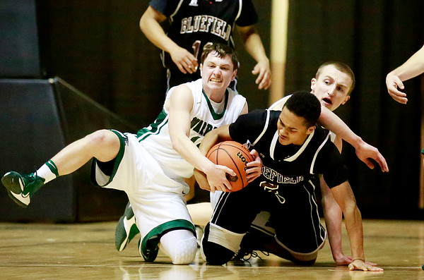 Wyoming East's Corey McKinney (14) tries to rip the ball from Bluefield's  Donta' Hopkins (2) as Wyoming East's Zachary Cook (24) struggles as well during their Big Atlantic game Tuesday in Beckley. (Chris Jackson/The Register-Herald)