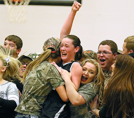 (Brad Davis/The Register-Herald) Westside's Makayla Morgan is mobbed by a hoard of camo-clad classmates as they rush the court following the Renegades' sectional championship win over county rival and defending state champion Wyoming East Wednesday night in Clear Fork.