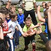 Quincy Wilson, former WVU football player, background, had the kid do a drill to slap the football during a youth football camp held in Coal City.<br /> (Rick Barbero/The Register-Herald)