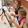 (Brad Davis/The Register-Herald) Young artists Kaylee (near), 10, and Taylor Wills, 17, make their won paintings during the Beckley Art Center's Family Art Festival Saturday afternoon.