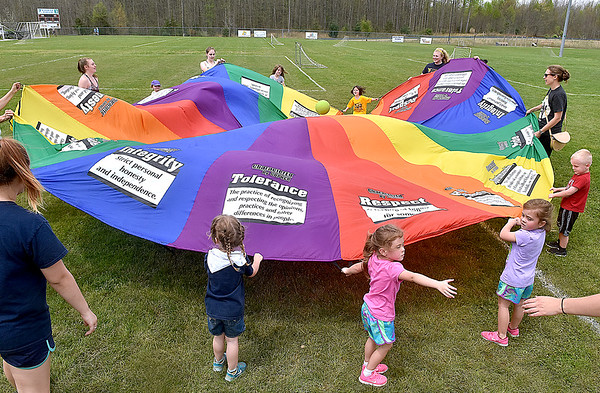 (Brad Davis/The Register-Herald) A combination of youngsters, WVU Tech women's soccer players and parents all work together to toss a ball around with a giant parachute during a YMCA Healthy Kids Day event Saturday afternoon at the YMCA Paul Cline Memorial Sports Complex.