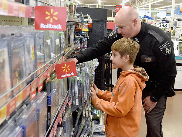 (Brad Davis/The Register-Herald) Nine-year-old Cool Ridge resident Dominick Foley gets some help searching for video games from Raleigh County Sheriff's Deputy J.A. Redden during a special Shop With a Deputy event Sunday afternoon at the MacArthur Walmart. Several Raleigh County Sheriff's Deputies and West Virginia State Troopers spent the day taking kids around the store with $100 budgets to spend on whatever they chose.