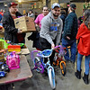(Brad Davis/The Register-Herald) Volunteer Adam Quesenberry carries new bikes for a customer during the annual Mac's Toy Fund event Saturday morning at the Beckley-Raleigh County Convention Center.