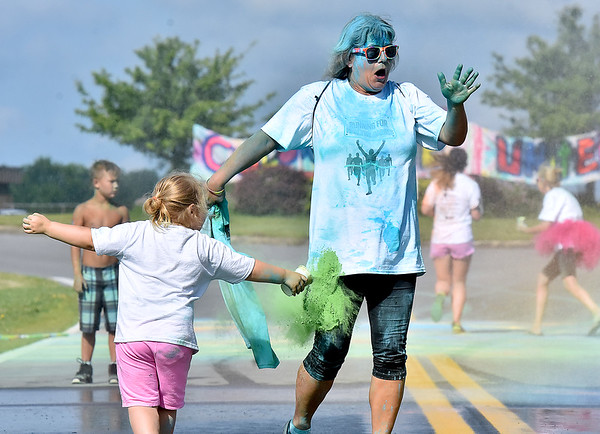 (Brad Davis/The Register-Herald) Young color bomber Azalea Sabo, 4, catches participant Lora Persinger during United Way of Southern West Virginia's annual Color Me United Walk/Run Saturday morning at the Raleigh County Memorial Airport.