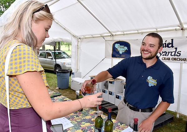 (Brad Davis/The Register-Herald) Daniel Vineyards' Rich Daniel pours a sample for Sarah Houck during Spring Wine Fest Saturday.
