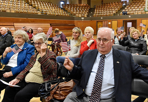 """(Brad Davis/The Register-Herald) Attendees, including several veterans and their families wave flags as the Fayetteville Community Chorus sings """"You're a Grand Old Flag"""" during Fayetteville's annual Veteran's Appreciation Day ceremony at the Fayette County Soldier's and Sailor's Memorial Building Sunday afternoon."""