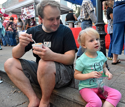 (Brad Davis/The Register-Herald) Dad Travis Doyle has some more chili while three-year-old daughter Felicity has already moved on to brownies for dessert during Beckley's annual Chili Night event Saturday evening.