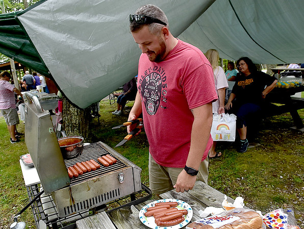 (Brad Davis/The Register-Herald) Humble grillmaster Lydon Lilly, a Virginia resident, keeps the hotdogs flowing during the annual Lilly Family Reunion Saturday afternoon near Ghent.
