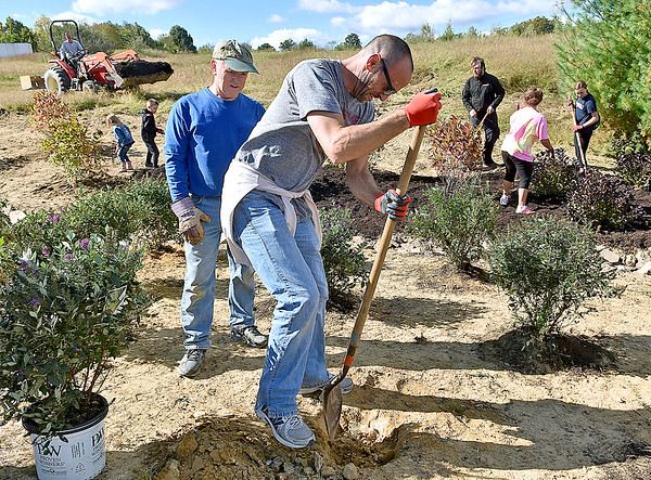 (Brad Davis/The Register-Herald) Brent Bledsoe digs away as he and a small army of fellow Piney Creek Watershed Association volunteers young and old work to construct a butterfly garden Saturday morning next to the YMCA Paul Cline Memorial Sports Complex.