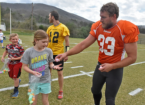 (Brad Davis/The Register-Herald) New Jersey resident Brooke Hannon, 9, gets a little help gathering Easter eggs from North tight end Jordan Thompson during an Easter egg hunt held at halftime of a Spring League game between teams North and South Sunday afternoon in White Sulphur Springs.