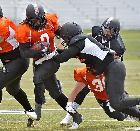 (Brad Davis/The Register-Herald) East (orange jerseys) running back Anthony Dixon rumbles ahead as West (black jerseys) linebacker Ridge Wilson tries to bring him down during the opening game of The Spring League Saturday afternoon in White Sulphur Springs.