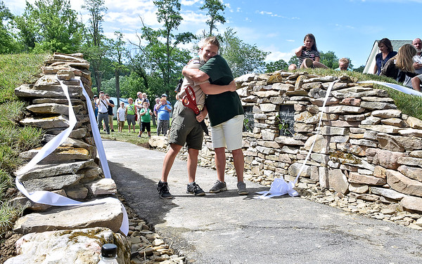 (Brad Davis/The Register-Herald) Boy Scout Cameron Zobrist, who hatched the idea for the memorial behind him after helping fellow residents through the struggle of recovery, gets a big hug from Audrey Van Buren after cutting the ribbon Friday afternoon at Old Mill Park.