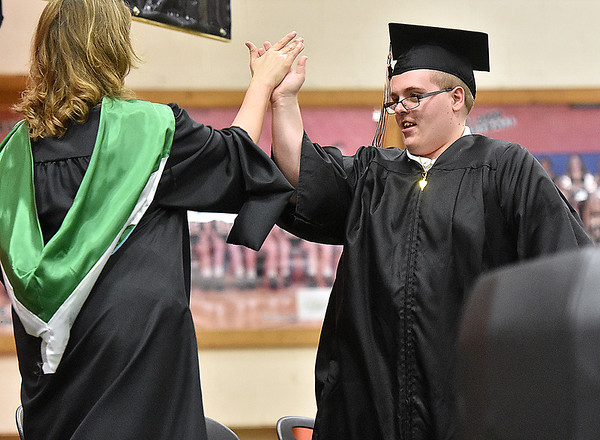(Brad Davis/The Register-Herald) Summers County High School graduate William Ballard gets a high-five from principal Kari Vicars as he and the rest of the 2017 class get their diplomas during the school's commencement ceremony Friday evening in Hinton.