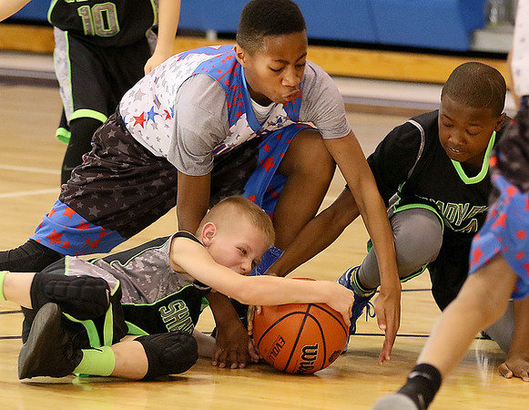 (Brad Davis/The Register-Herald) Shady Elite players Jake Pate, left, and Ammar Maxwell dive for a loose ball with Ward 5's (Washington, D.C.) Holden Pieere-Lewis during biddy buddy action Saturday.