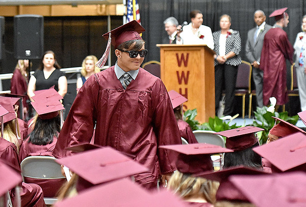 (Brad Davis/The Register-Herald) Woodrow Wilson senior Austin Henderson rocks shades for the event as he makes his way back his seat after collecting his diploma during the school's 91st Commencement Saturday evening at the Beckley-Raleigh County Convention Center.